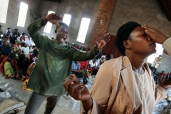 Worshippers pray for a woman possessed by a demon during a mass in Bukavu, DR Congo - August 7, 2007