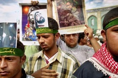KARBALA, IRAQ - April 2003 : Iraqi Shia men carry portraits of Imam Hussein around the Holy Mosque of Imam Hussein in the center of Karbala, Iraq. Iraqi Shia Muslims traveled to the holy city of Karbala to commemorate the 40th day after the death of Imam Hussein, the grandson of the Prophet Mohammed, over 1,400 years ago. The ceremony was banned under ousted Iraqi President Saddam Hussein.